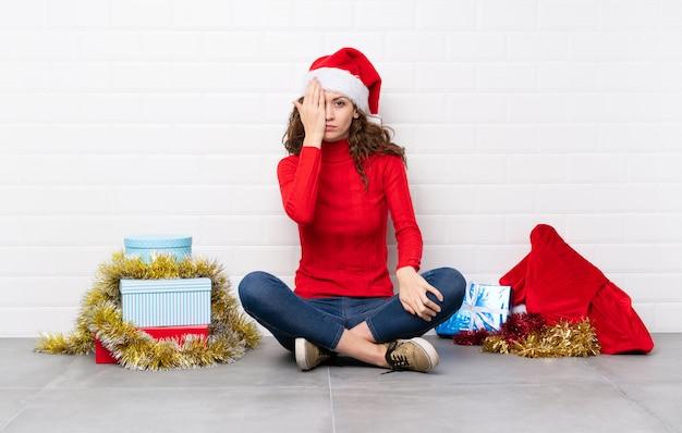 Fille en vacances de noël assis sur le sol couvrant un oeil à la main