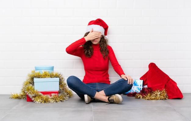 Fille en vacances de noël assis sur le sol, couvrant les yeux par les mains