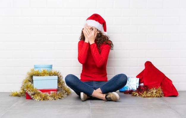 Fille en vacances de noël assis sur le sol, couvrant les yeux et regardant à travers les doigts