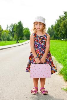 Fille avec valise debout sur la route