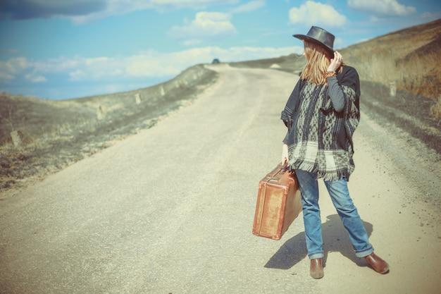Fille avec une valise sur la route