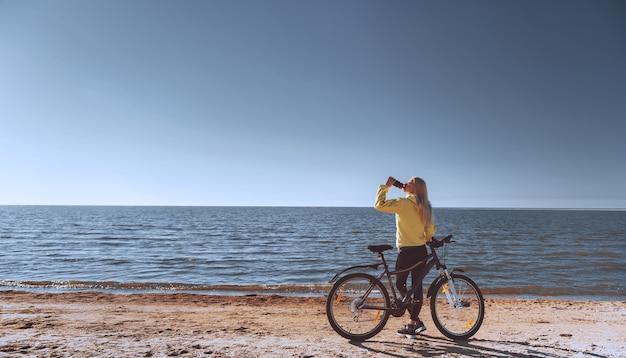 Une fille à vélo au bord de la mer