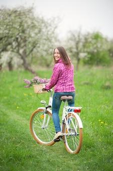 Fille sur un vélo blanc vintage avec panier de fleurs lilas dans un jardin de printemps