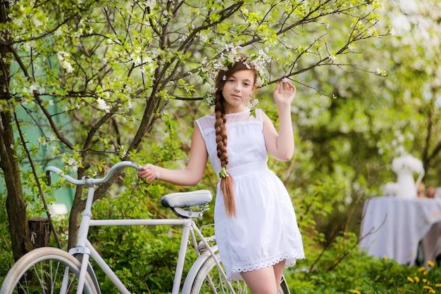 Fille avec le vélo et une couronne de fleurs sur la tête