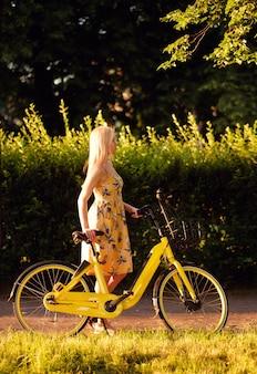 Fille avec vélo électrique jaune dans le parc