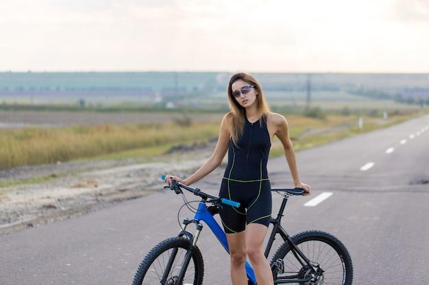 Fille sur un vélo de montagne sur tout-terrain beau portrait d'une fille cycliste monte un vélo en carbone moderne