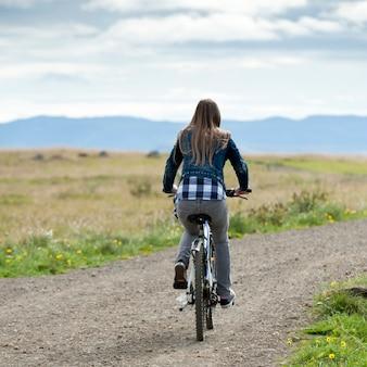Fille en vélo sur une route de campagne non pavée