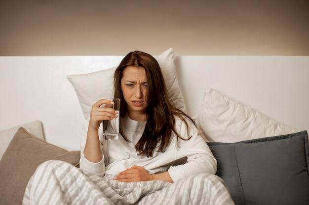 Fille avec un verre d'eau est assise dans son lit et tient l'estomac malade