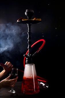 Une fille avec un verre de vin rouge fume un narguilé aux fruits