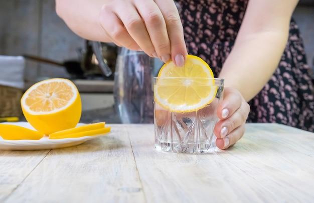 La fille verse de l'eau avec du citron. mise au point sélective. boisson.