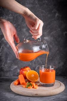 Fille verse le jus de carotte et d'orange à partir d'une cruche dans un verre sur une planche ronde en bois dans un low key