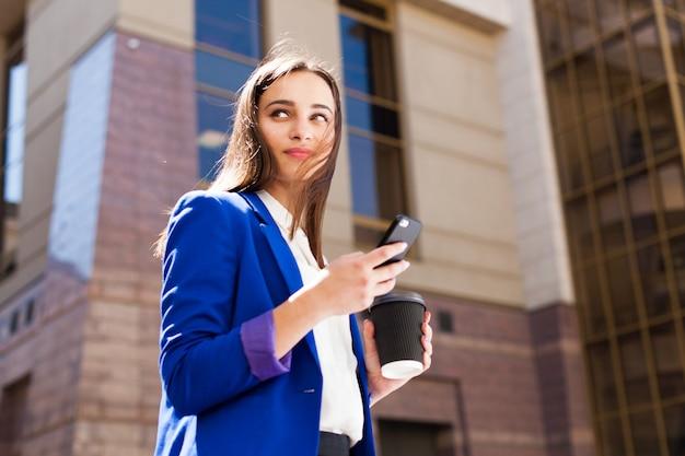 Une fille en veste bleu brillant se tient debout avec un smartphone et un café dans la rue