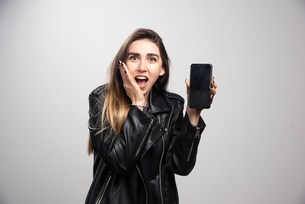 Fille en veste de cuir tenant un téléphone intelligent sur fond gris.