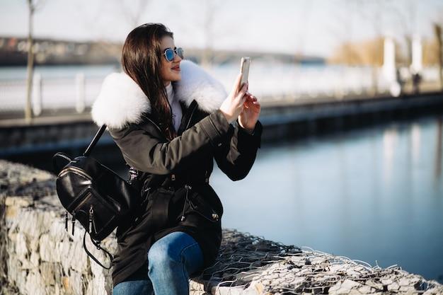 Fille en veste de fourrure, parler au téléphone à l'extérieur au bord du lac