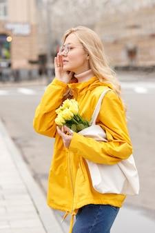 Fille en veste jaune avec des fleurs dans un sac écologique dans la ville en automne