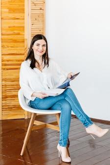 Une fille en veste légère de jeans est assise chaise avec un magazine dans ses mains, mode, lecture, divertissement, profession, éditeur, pigiste, accueil
