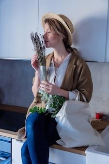 Fille en veste avec sac fourre-tout et plantes dans une cuisine