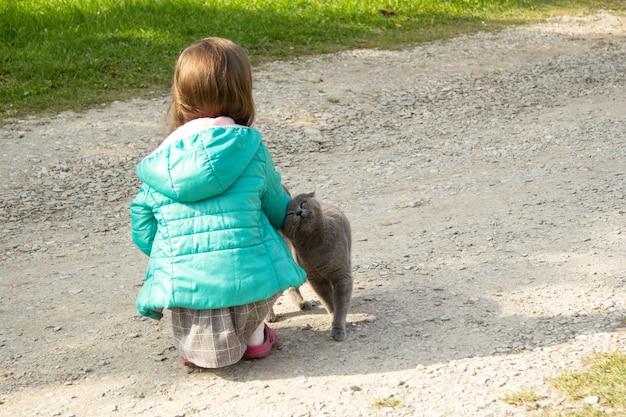 Une fille en veste verte assise avec son gros chat gris dans la rue le chat caresse l'enfant