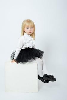 Fille en vêtements d'automne pose sur blanc