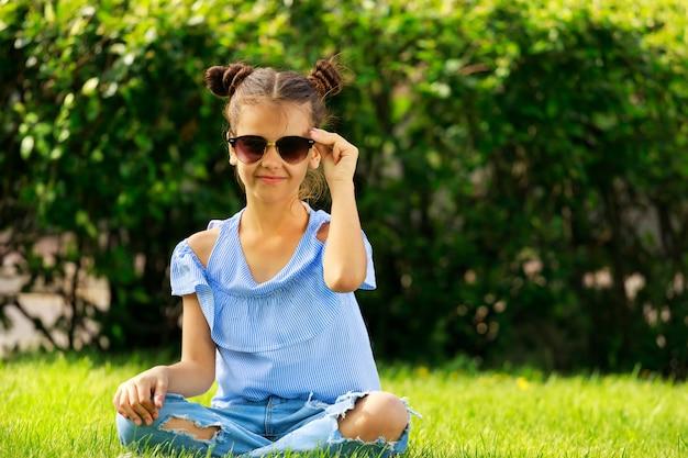 Une fille en vêtements bleus est assise sur l'herbe en été dans le parc. un enfant en lunettes de soleil. photo de haute qualité