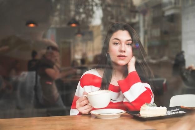 Fille en vêtements décontractés assis dans un café à la fenêtre avec une tasse de café et une assiette de gâteau