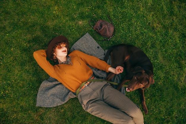 Fille en vêtements élégants et chapeau se trouve sur la pelouse avec le chien