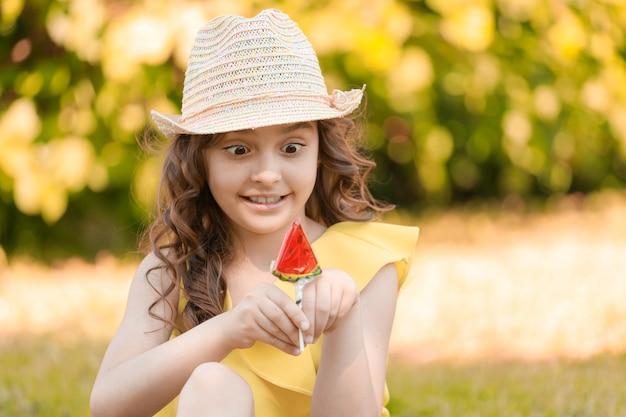 Une fille en vêtements jaunes et un chapeau est assise sur l'herbe dans le parc en été avec une sucette en forme de tranche de pastèque. photo de haute qualité