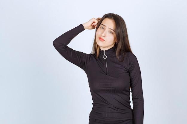 Fille en vêtements noirs a l'air réfléchie et douteuse.