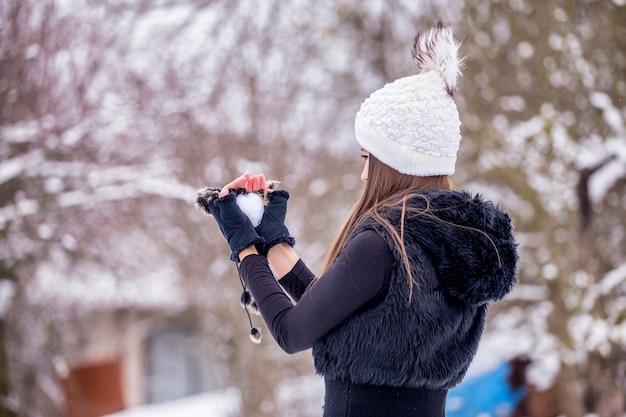 Une fille en vêtements noirs et un bonnet tricoté blanc en hiver