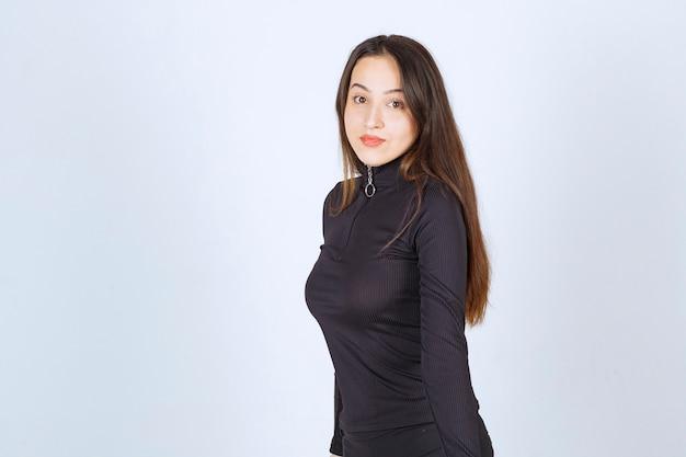 Fille en vêtements noirs donnant des poses professionnelles et neutres sans réaction.