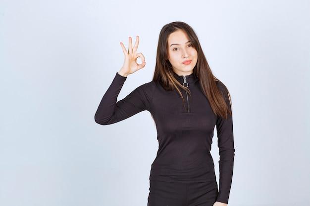 Fille en vêtements noirs montrant le signe de la jouissance du cercle.