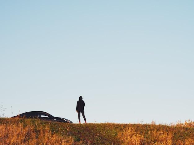 Une fille en vêtements noirs se tient à côté d'une berline noire sur une colline, contre un ciel sombre, copiez l'espace.