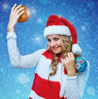 Fille vêtue d'un bonnet de noel tenant des boules de décoration de noël. elle regarde la caméra. concept de vacances avec fond bleu.