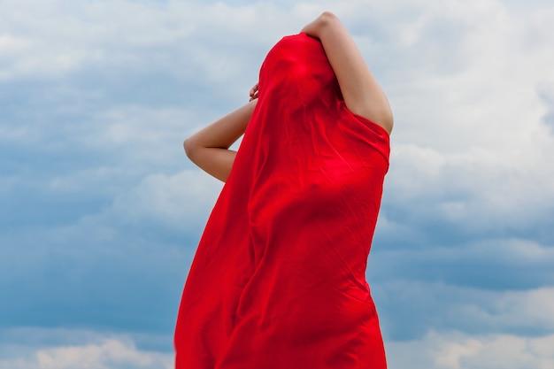 Une fille vêtue d'un drap rouge sur le sable pose pour un photographe sur fond de ciel nuageux. le tissu rouge au vent épouse la silhouette de la fille.