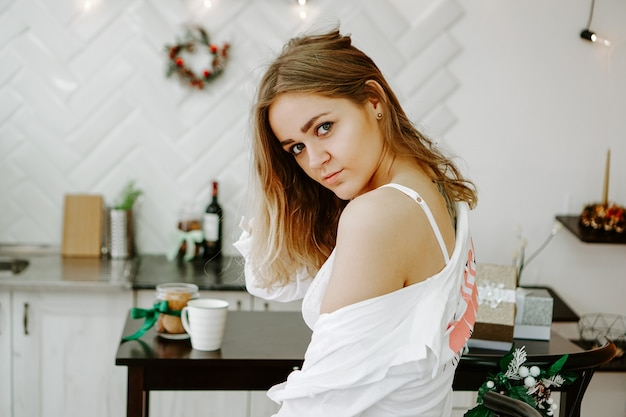 Une fille vêtue d'une longue chemise blanche se tient dans la cuisine. la cuisine blanche est décorée de décorations de noël et de guirlandes
