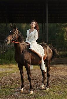 Fille vêtue d'une longue robe à cheval, une belle femme à cheval dans un champ en automne. vie à la campagne et mode, noble destrier
