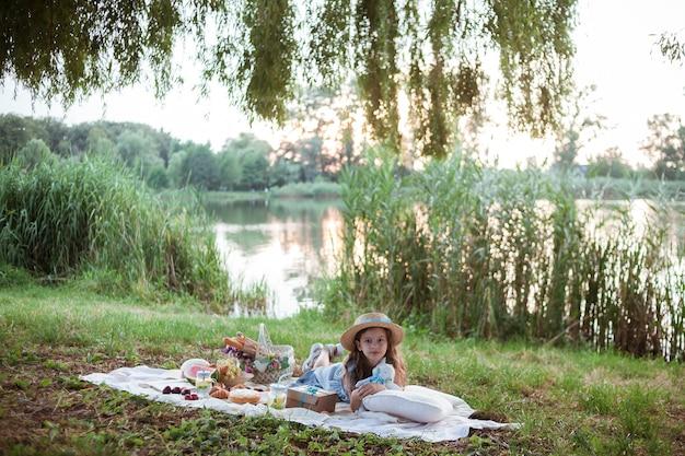 Une fille vêtue d'une robe aux cheveux longs est sur une couverture blanche avec un panier de fruits et de pâtisseries avec des fleurs