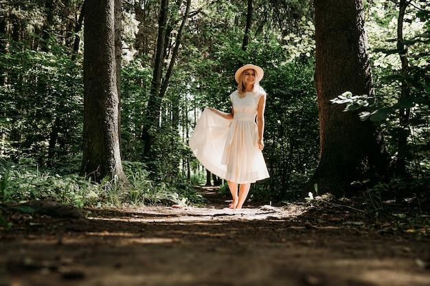 Une fille vêtue d'une robe blanche et d'un chapeau se promène dans un parc ou une forêt d'été. forêt de fées. photo pleine longueur d'une femme heureuse