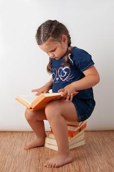 Une fille vêtue d'une robe en jean bleu est assise sur une pile de livres et tient un livre ouvert sur ses genoux. un enfant heureux lit, isolé