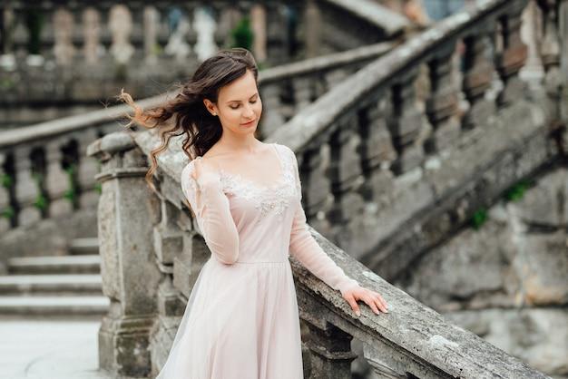 Une fille vêtue d'une robe rose clair dans la perspective d'un château de pierre polonais médiéval