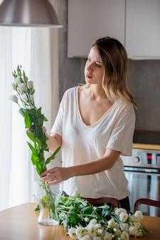 Une fille vêtue d'un t-shirt blanc prépare un bouquet de roses blanches avant de les mettre dans un vase sur la table de la cuisine. concept de mode de vie