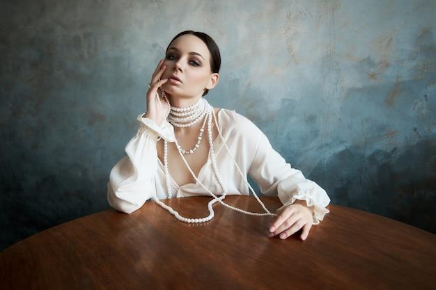 Fille vêtue de vêtements boho blancs avec des perles de perles blanches autour du cou est assise à une table