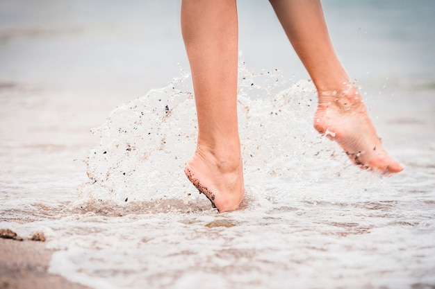 Fille vient pieds nus dans l'eau en mer