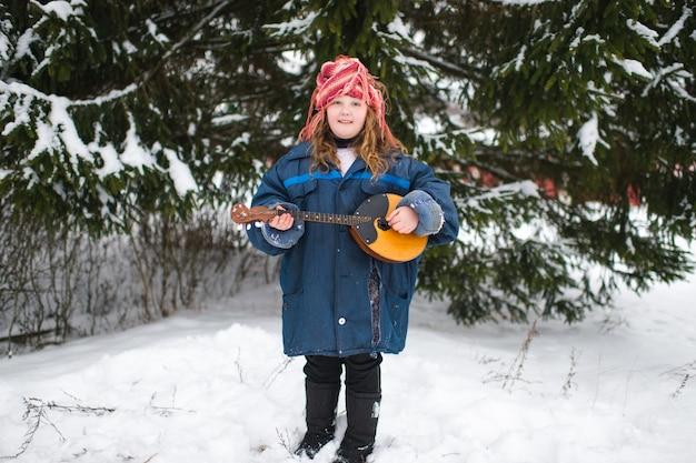 Fille de village assez caucasien dans des vêtements chauds et bonnet tricoté