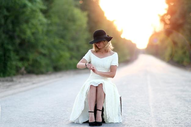 Fille vintage avec chapeau avec montre avec une valise faisant de l'auto-stop en attente
