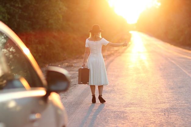Fille vintage avec chapeau avec une valise faisant de l'auto-stop en voiture
