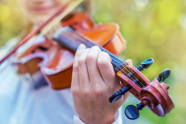 Fille avec un violon sur un flou lumineux du bokeh