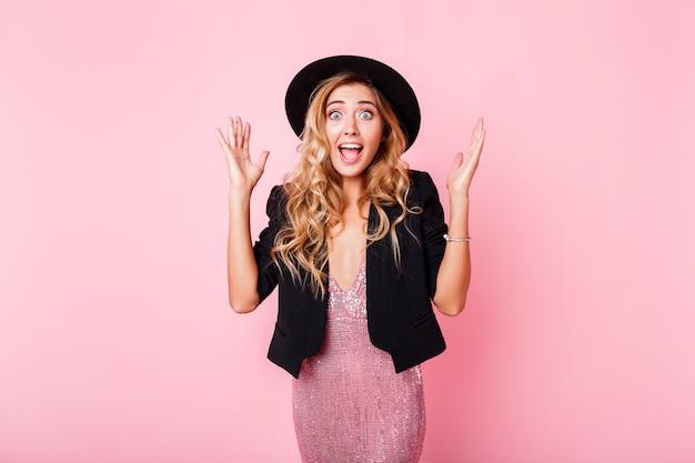 Fille avec visage surprise debout sur un mur rose. porter une robe élégante avec des paillettes. émotions émerveillées porter une robe tendance avec séquence, veste noire et chapeau.