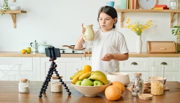 Une fille vlogueuse enregistre du contenu vidéo pour un blog culinaire, une fille joyeuse partage ses secrets à l'antenne