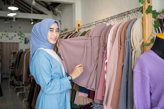 Une fille voilée tient des vêtements à offrir en se tenant debout